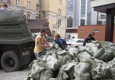 Грузчики загружают мусорные пакеты