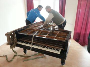 Грузчики пакуют рояль